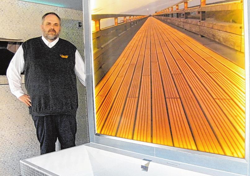Jan-Dirk Haskamp stellt ein Bad vor, auf dessen Rückseite ein beleuchtetes Bild der Heiligenhafener Seebrücke zu sehen ist. FOTO: BG